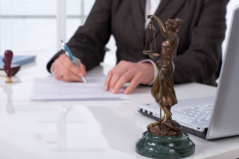 Woman writing near the statue of Lady Justice representing legal translation portfolio