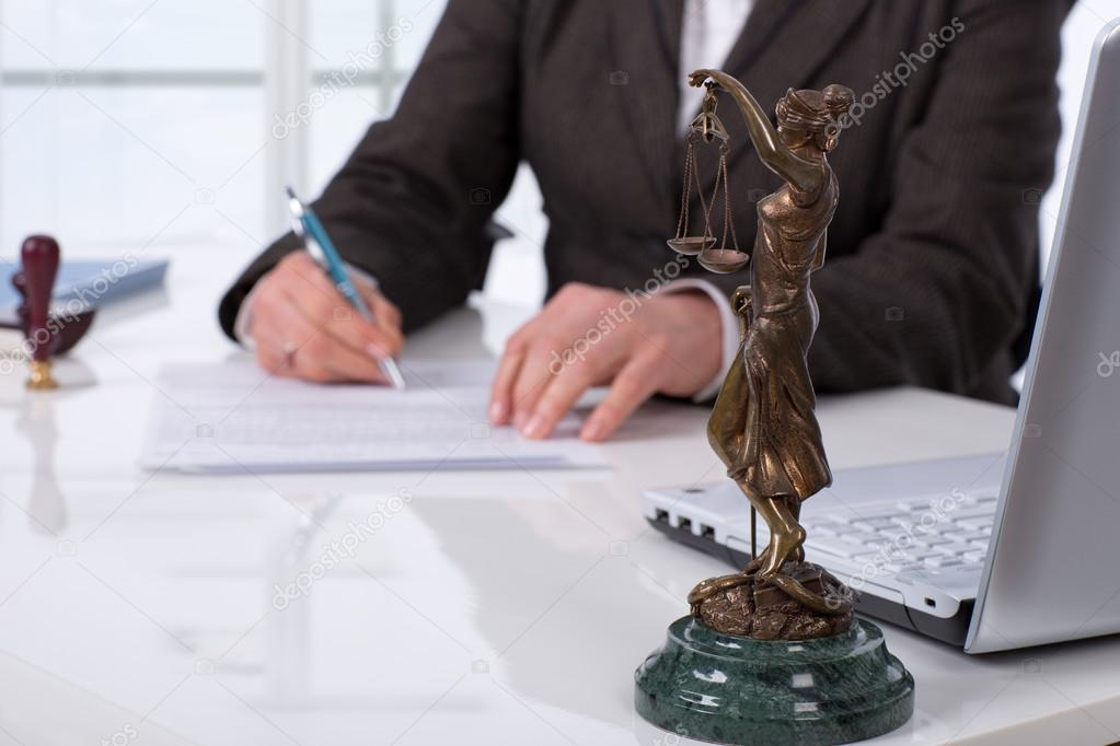 Woman signing a contract next to Lady Justice statue representing legal translations